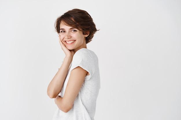 Retrato de uma jovem natural com cabelo curto, tocando a pele pura e limpa e sorrindo, em pé contra uma parede branca