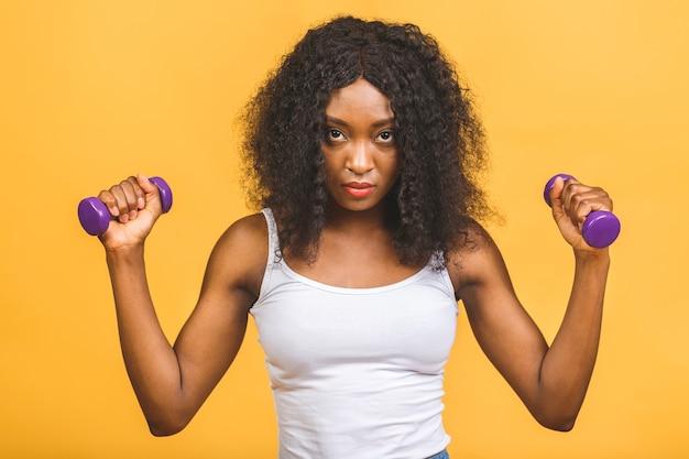 Retrato de uma jovem negra afro-americana exercitando seus músculos com halteres