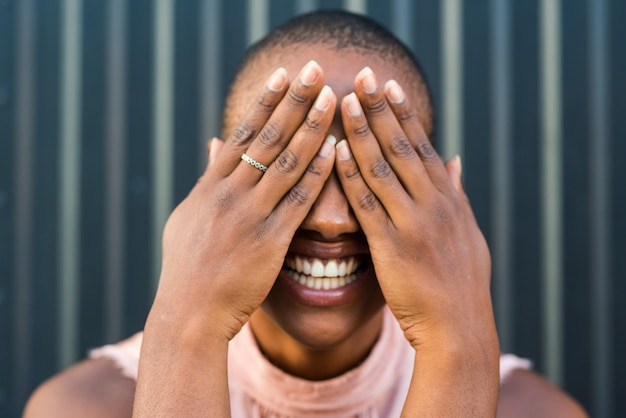 Retrato de uma jovem negra alegre africana ou americana, sorrindo para a câmera com as mãos nos olhos, cobrindo-o
