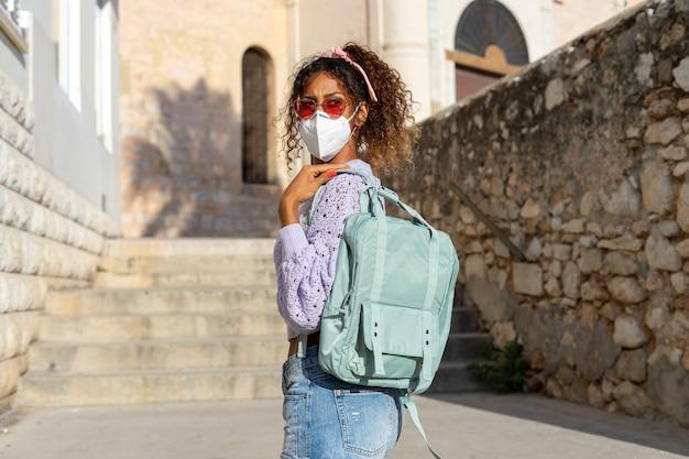 Retrato de uma jovem negra atraente andando com mochila e máscara. passeios turísticos