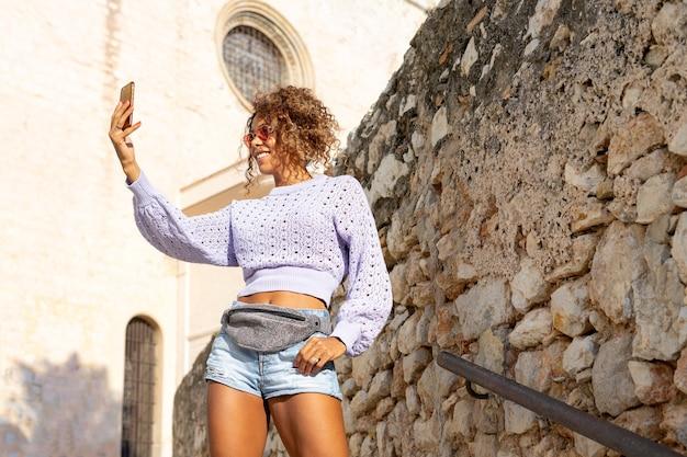 Retrato de uma jovem negra atraente, tirando uma selfie com o celular. falando no telefone