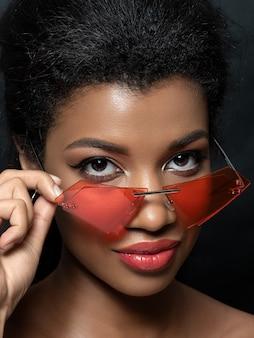 Retrato de uma jovem negra linda olhando para óculos de sol vermelhos da moda moderna