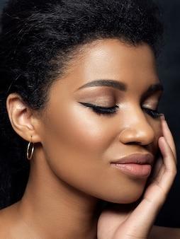 Retrato de uma jovem negra linda tocando seu rosto. limpeza da pele, cuidados com a pele, conceito de cosmetologia