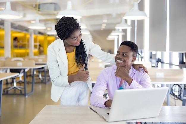 Retrato de uma jovem negra sorrindo em um ambiente de trabalho com cadernos, empresário africano ou estudante