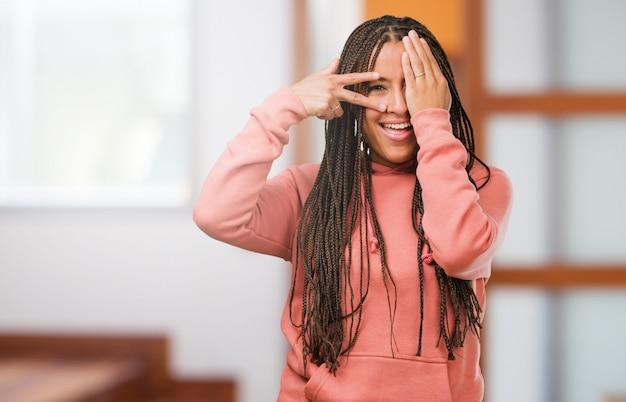 Retrato de uma jovem negra vestindo tranças sente-se preocupado e assustado, olhando e cobrindo o rosto, conceito de medo e ansiedade