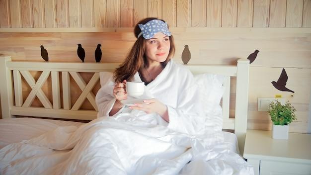 Retrato de uma jovem no banheiro deitada em um quarto de hotel e bebendo café