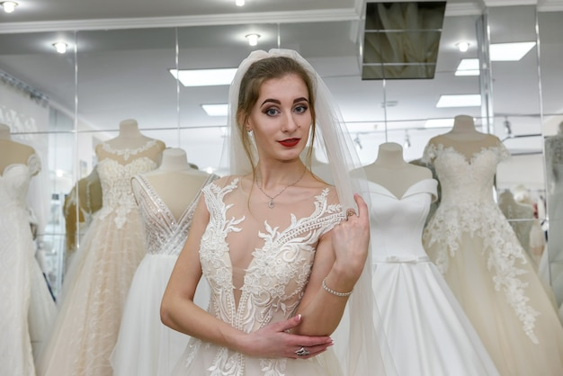 Retrato de uma jovem noiva em um vestido de noiva em uma loja
