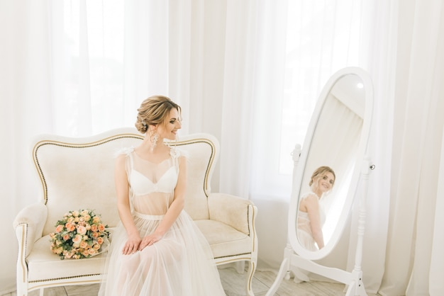 Retrato de uma jovem noiva linda em um quarto luminoso em uma atmosfera romântica. noiva em uma camisa de noite com um buquê de casamento