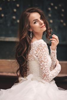 Retrato de uma jovem noiva linda em um vestido de noiva branco com cabelo comprido na velha cidade europeia