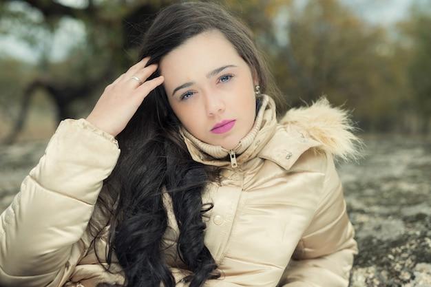 Retrato de uma jovem olhando pensativamente para a câmera