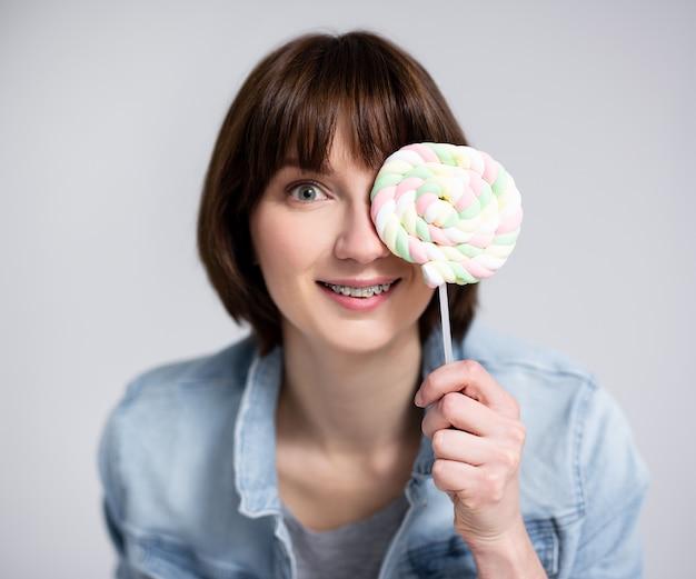 Retrato de uma jovem ou adolescente engraçada cobrindo o rosto com pirulito sobre fundo cinza