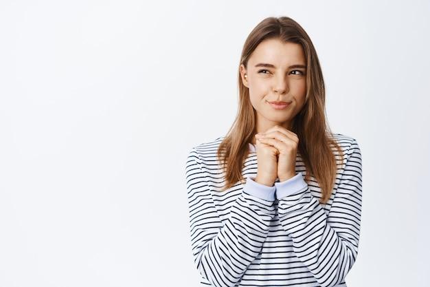 Retrato de uma jovem pensativa com cabelo loiro, piscando pensativo, tendo uma ideia interessante, olhando para a esquerda no espaço da cópia, em pé sobre uma parede branca