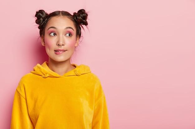 Retrato de uma jovem pensativa com dois coques de cabelo, morde os lábios, mergulhada em pensamentos, tenta encontrar uma solução em mente, vestida com um macacão amarelo