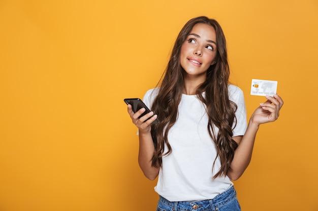 Retrato de uma jovem pensativa com longos cabelos castanhos em pé sobre uma parede amarela, segurando um telefone celular, mostrando um cartão de crédito de plástico