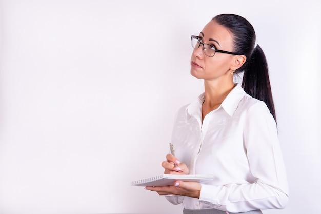 Retrato de uma jovem pensativa de óculos, olhando para o espaço isolado no branco
