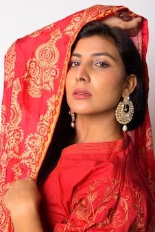 Retrato de uma jovem persa linda vestindo roupas tradicionais contra uma parede branca