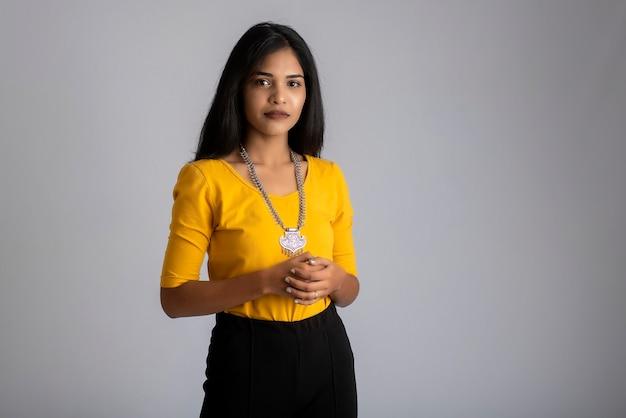 Retrato de uma jovem posando em cinza