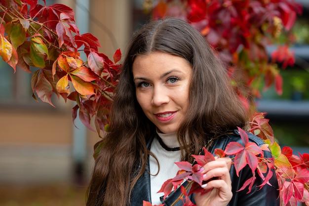 Retrato de uma jovem positiva com cabelo comprido, posando na parede vermelha de ivy de outono ao ar livre