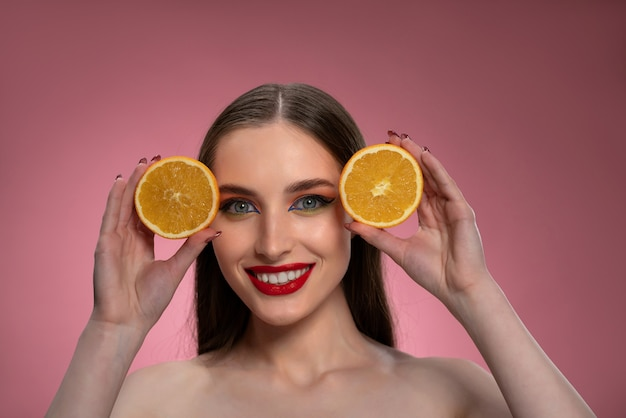 Retrato de uma jovem positiva com laranjas cortadas nas mãos, parecendo encantador