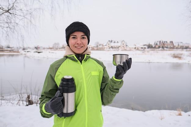 Retrato de uma jovem positiva com uma jaqueta verde segurando uma garrafa térmica e bebendo chá quente no lago de inverno
