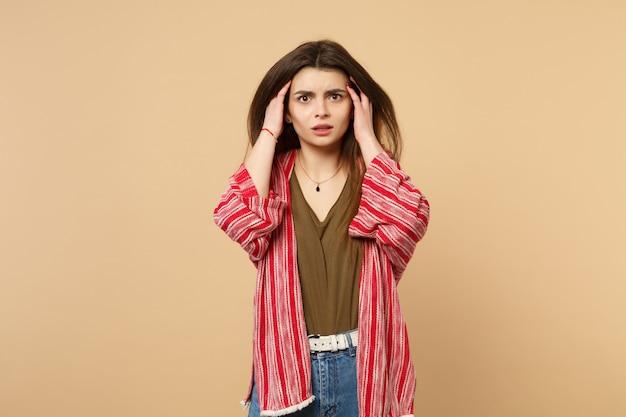 Retrato de uma jovem preocupada chocada em roupas casuais, colocando as mãos na cabeça isolada no fundo da parede bege pastel em estúdio. emoções sinceras de pessoas, conceito de estilo de vida. simule o espaço da cópia.