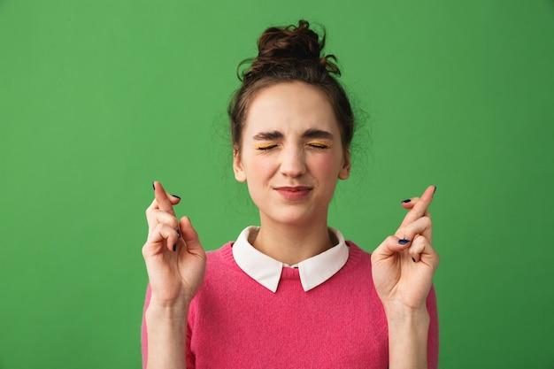Retrato de uma jovem preocupada, isolada, com os dedos cruzados para dar sorte