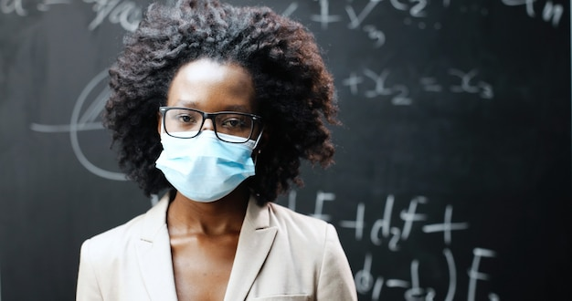 Retrato de uma jovem professora afro-americana de óculos e máscara médica, olhando para a câmera na sala de aula. quadro-negro com fórmulas no fundo. conceito de coronavírus. escolaridade pandêmica.