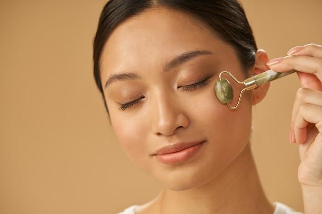 Retrato de uma jovem relaxada usando o rolo de jade para massagear o rosto, posando com os olhos