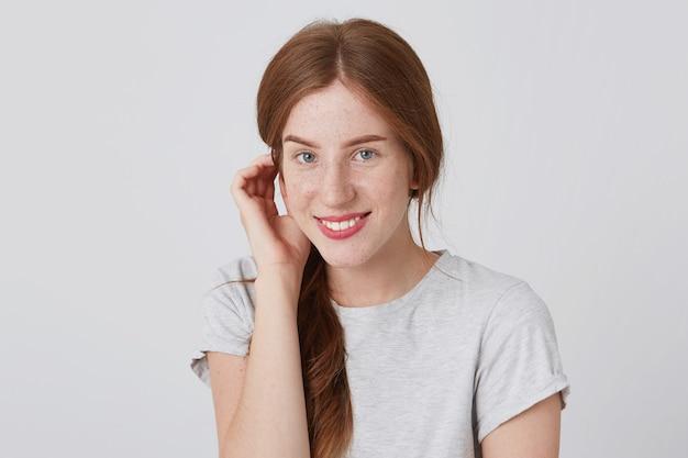 Retrato de uma jovem ruiva adorável e feliz com sardas usando uma camiseta cinza tocando sua orelha