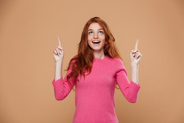 Retrato de uma jovem ruiva alegre apontando para cima com os dedos