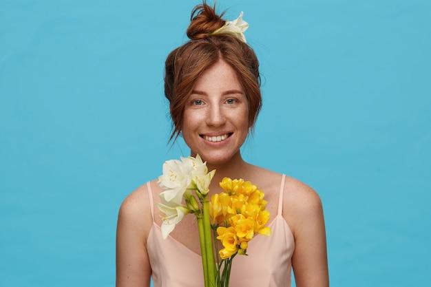 Retrato de uma jovem ruiva alegre com maquiagem natural, olhando para a câmera com um sorriso encantador e segurando um buquê de flores, isolado sobre fundo azul
