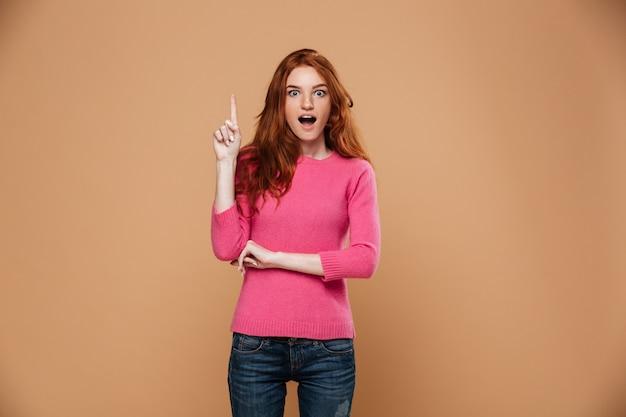 Retrato de uma jovem ruiva animado apontando para cima com os dedos