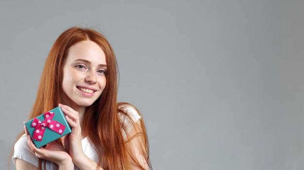 Retrato de uma jovem ruiva atraente de pé isolado, segurando uma caixa de presente