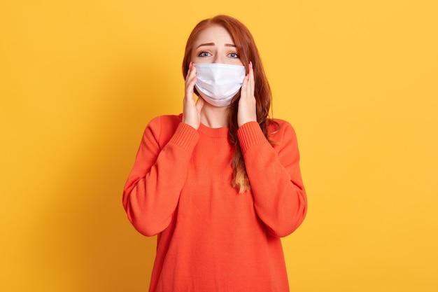 Retrato de uma jovem ruiva com belos olhos, tendo dor de cabeça, segurando as mãos nas bochechas, usando máscara médica contra gripe e suéter laranja isolado sobre fundo amarelo.
