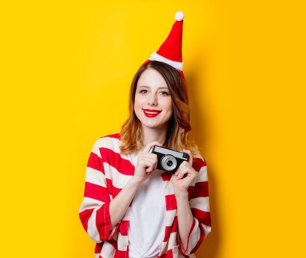 Retrato de uma jovem ruiva com chapéu de papai noel e camisa listrada com câmera clássica em fundo amarelo. época de natal