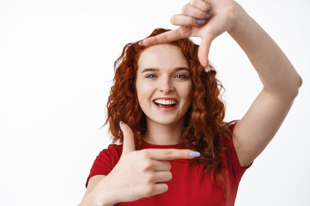 Retrato de uma jovem ruiva criativa mostrando gesto de moldura com a mão, tirando uma foto de você com um rosto sorridente e feliz, em pé com uma camiseta contra a parede branca