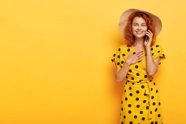 Retrato de uma jovem ruiva de aparência agradável e satisfeita mantém as palmas das mãos no peito, fica impressionado ao ouvir uma história de cortar o coração ao longo do smartphone e usa um elegante traje de verão amarelo brilhante