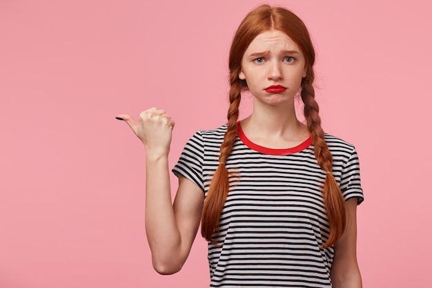 Retrato de uma jovem ruiva de olhos azuis parece triste, chateada, frustrada, apontando com o polegar para o lado esquerdo no espaço em branco da cópia, descontente com alguma coisa, beicinho, expressão de insulto, na parede rosa