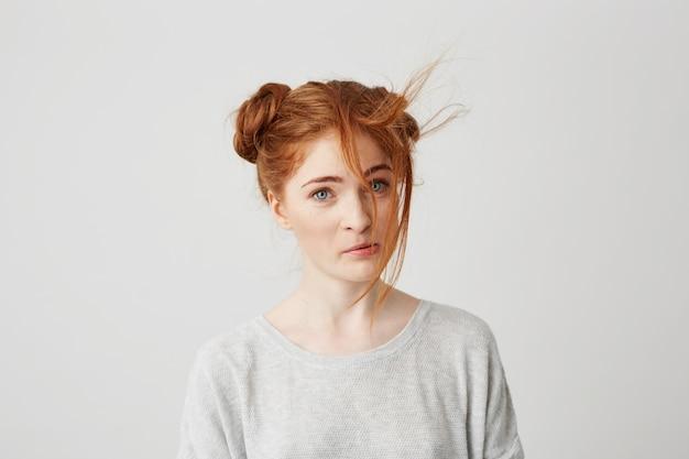 Retrato de uma jovem ruiva linda com bolo de cabelo mimado.