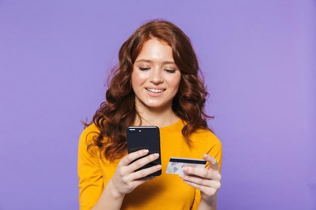 Retrato de uma jovem ruiva muito alegre em pé sobre a violeta, usando o celular, mostrando o cartão de crédito