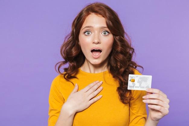 Retrato de uma jovem ruiva muito animada em pé sobre a violeta, mostrando um cartão de crédito de plástico