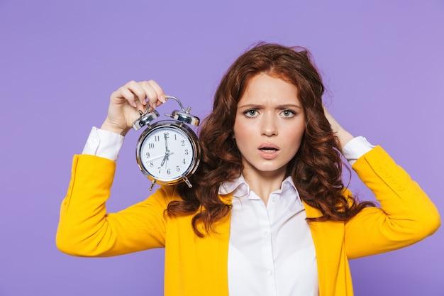 Retrato de uma jovem ruiva muito chateada de pé sobre a violeta, segurando um despertador
