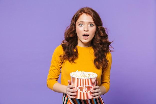 Retrato de uma jovem ruiva muito chocada em pé sobre a violeta