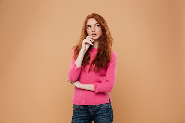 Retrato de uma jovem ruiva pensativa olhando para longe