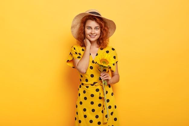 Retrato de uma jovem ruiva posando em vestido de polca amarela e chapéu de palha