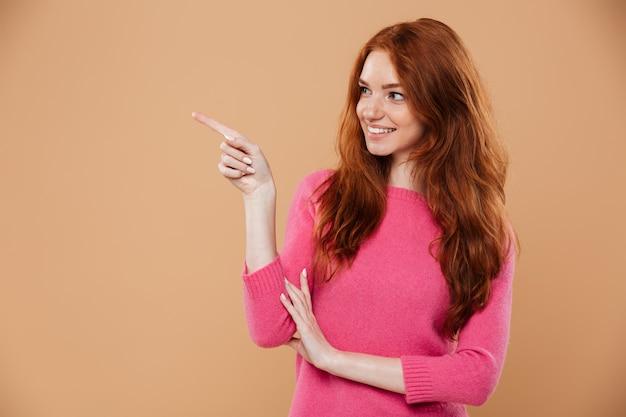 Retrato de uma jovem ruiva sorridente, apontando o dedo na parede copyspace