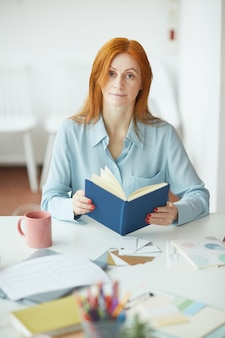 Retrato de uma jovem sardenta segurando um planejador no local de trabalho do designer