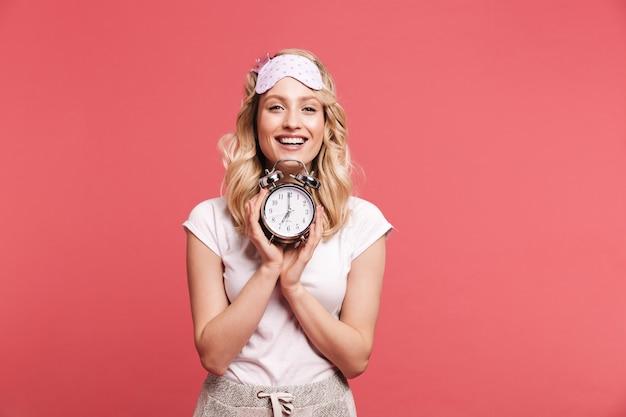 Retrato de uma jovem satisfeita usando uma máscara de dormir segurando um despertador após acordar, isolado sobre uma parede vermelha