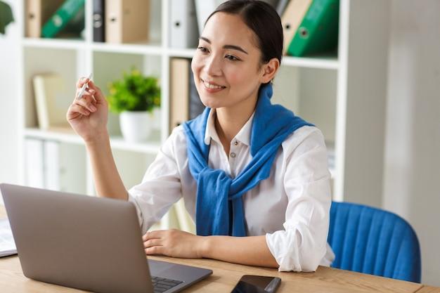 Retrato de uma jovem secretária asiática sentada à mesa e usando o laptop enquanto trabalhava no escritório