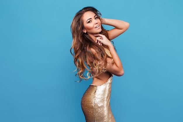 Retrato de uma jovem sedutora em um vestido dourado contra um fundo azul.
